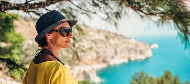 Frau, die auf klippe unter dem baum steht und zu einem meer schaut