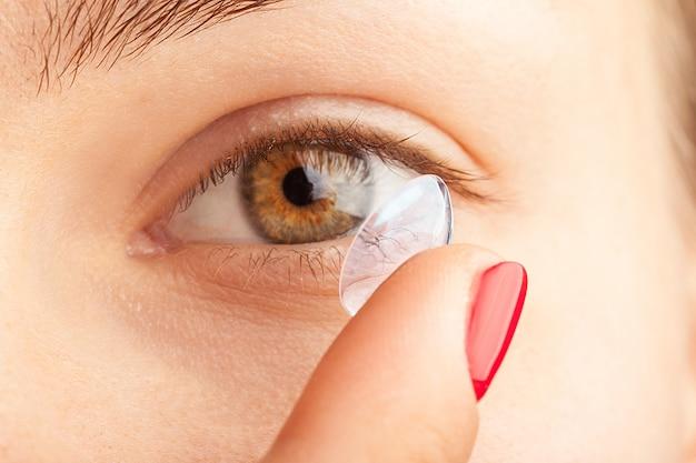 Frau, die auf kontaktlinsen sich setzt