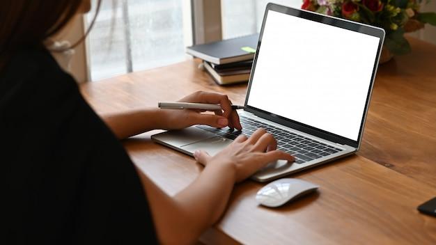 Frau, die auf laptop-computer mit leerem bildschirm schreibt
