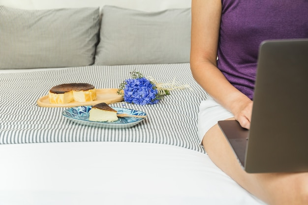 Frau, die auf laptop mit stück kuchen und blumenstraußblume im urlaub arbeitet.