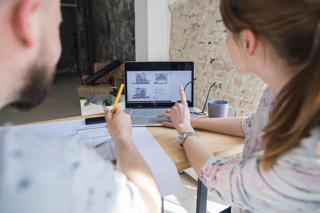 Frau, die auf laptopschirm beim arbeiten mit ihrem kollegen am arbeitsplatz zeigt