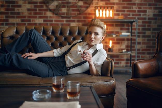 Frau, die auf ledercouch liegt und zigarre raucht