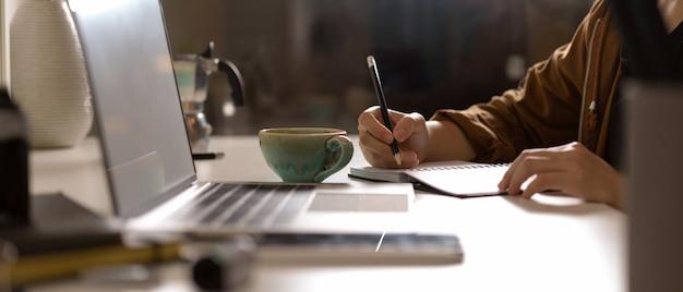 Frau, die auf leerem zeitplanbuch auf weißem tisch mit modell-laptop und zubehör im studio zur kenntnis nimmt