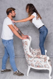 Frau, die auf lehnsessel steht und mit mann spricht