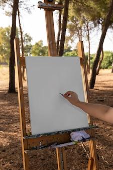Frau, die auf leinwand vor dem malen skizziert