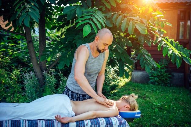 Frau, die auf massagebett im grünen garten des spa-zentrums liegt