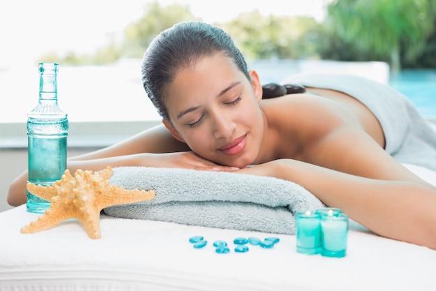 Frau, die auf massagetabelle in der badekurortmitte liegt