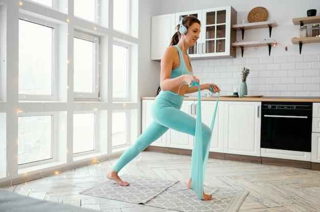 Frau, die auf matte mit gummiband trainiert