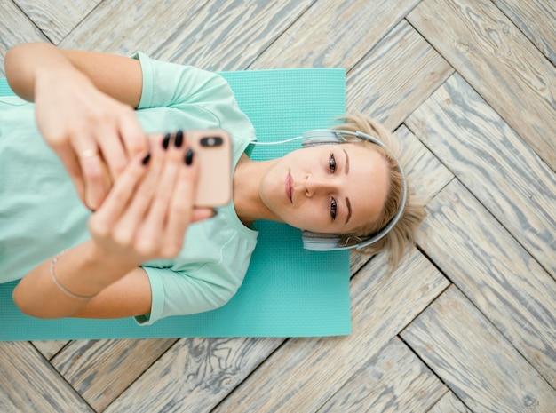 Frau, die auf matte trainiert und telefon benutzt