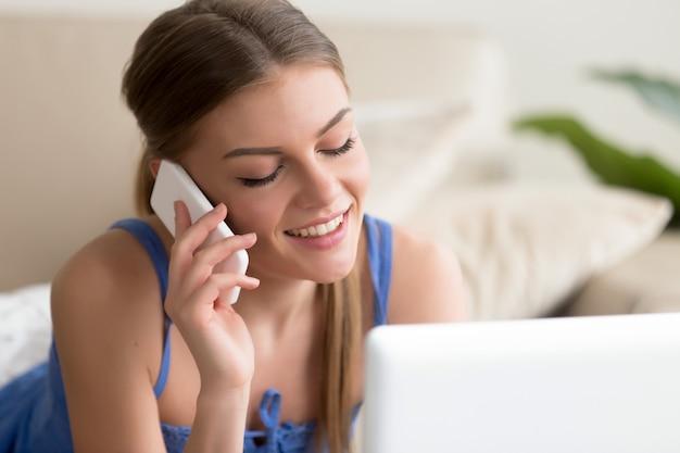 Frau, die auf mobiltelefon bei der anwendung des laptops spricht