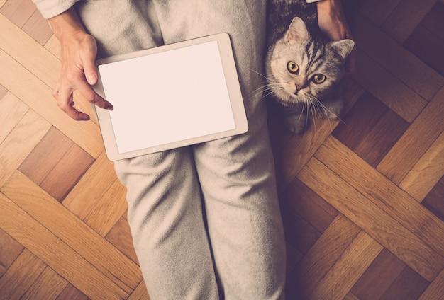 Frau, die auf netter katze des bodens sitzt und tablette, suchinternet, on-line-einkaufen betrachtet