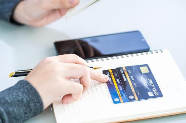 Frau, die auf notizbuch mit kreditkarte und smartphone-schreibtisch schreibt