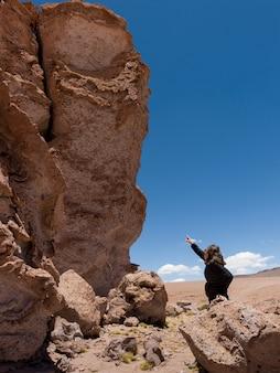 Frau, die auf pakana-mönch, salar de atacama, san- pedro de atacama, el loa province, antofagasta zeigt