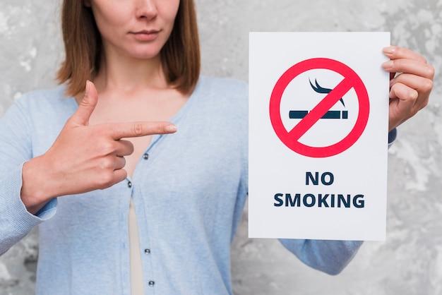 Frau, die auf papier mit nichtraucherzeichen und text zeigt