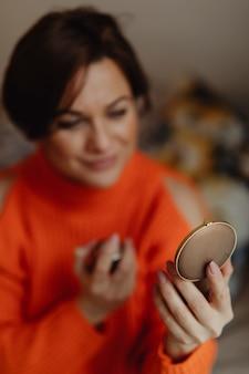 Frau, die auf parfüm sich setzt