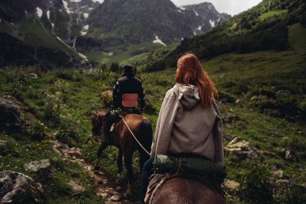 Frau, die auf pferd in bergen mit rucksack wandert