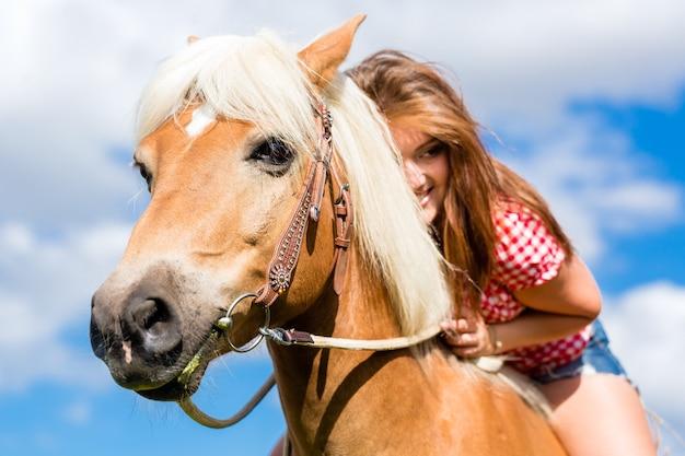 Frau, die auf pferd in der sommerwiese reitet