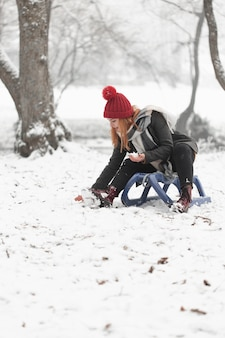 Frau, die auf pferdeschlitten sitzt und mit schnee spielt