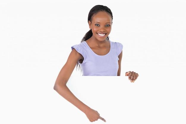 Frau, die auf platzhalter unter ihr auf weißem hintergrund zeigt
