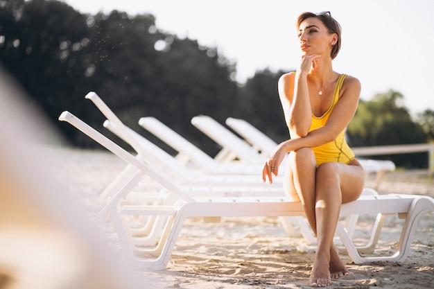 Frau, die auf poolbett durch das meer sitzt