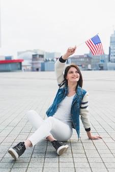 Frau, die auf quadrat sitzt und in der hand amerikanische flagge wellenartig bewegt