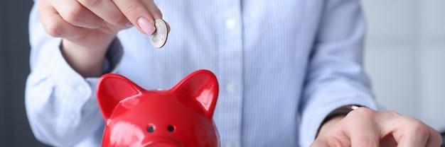 Frau, die auf rechner zählt und münze in sparschwein-nahaufnahme setzt.