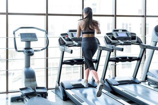 Frau, die auf rennstrecke im sportverein läuft