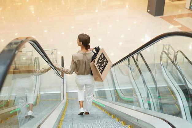 Frau, die auf rolltreppe steht