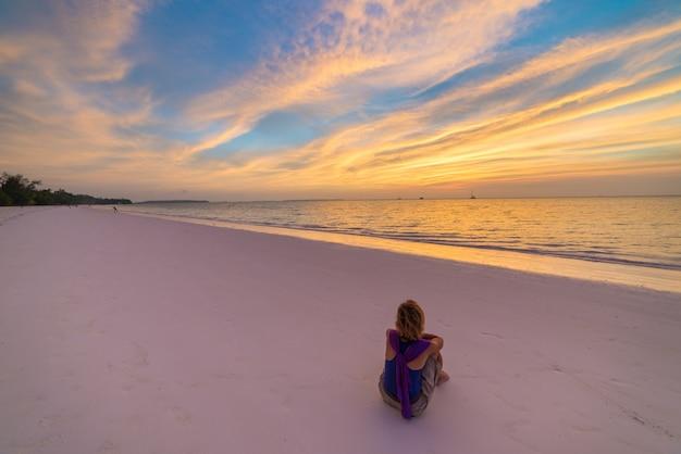 Frau, die auf romantischem himmel des sandstrandes bei sonnenuntergang, hintere ansicht, goldenes cloudscape, wirkliche leute sich entspannt. indonesien, kei-inseln, molukken maluku