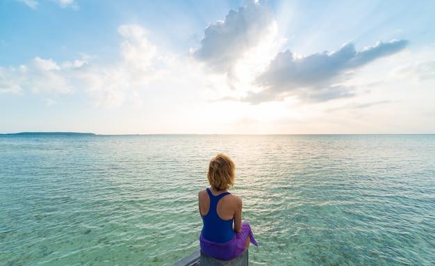 Frau, die auf romantischem himmel des sandstrandes bei sonnenuntergang, hintere ansicht, hintergrundbeleuchtung, wirkliche leute sich entspannt. indonesien, kei-inseln, molukken maluku
