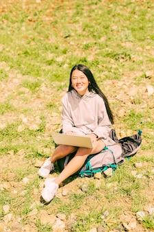 Frau, die auf rucksack mit notizbuch sitzt und kamera betrachtet