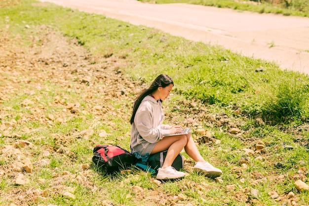 Frau, die auf rucksack sitzt und im laptop entlang straße arbeitet