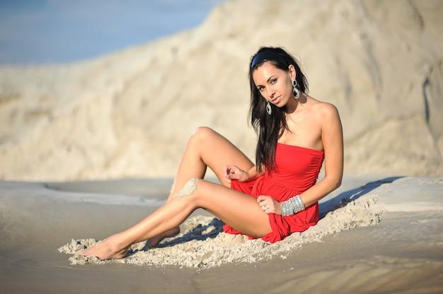 Frau, die auf sand im roten kleid kühlt