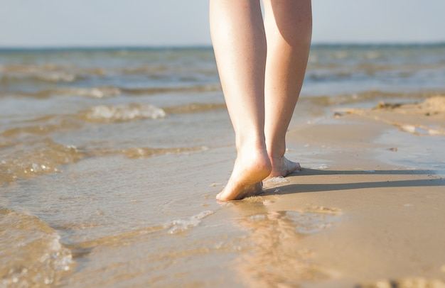 Frau, die auf sandstrand geht und fußabdruck im sand hinterlässt