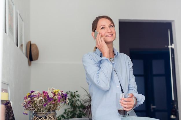 Frau, die auf schreibtisch steht und auf smartphone spricht