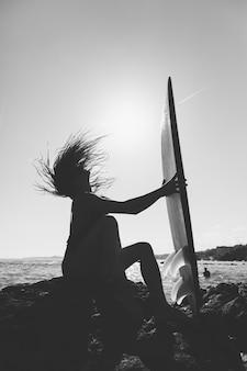 Frau, die auf seeufer mit surfbrett sitzt und haar rüttelt