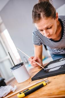Frau, die auf segeltuch malt