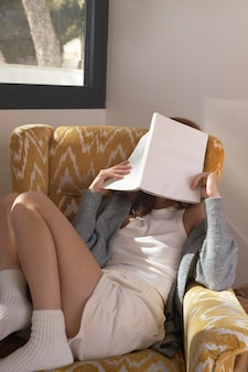 Frau, die auf sessel vollen schuss liest