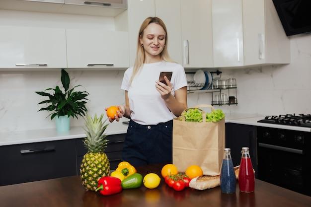 Frau, die auf smartphone beim stehen in der küche nach dem einkaufen schaut