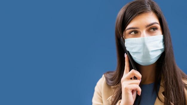 Frau, die auf smartphone spricht, während medizinische maske trägt