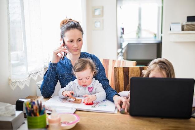 Frau, die auf smartphone während ihre kinder spielen über schreibtisch spricht