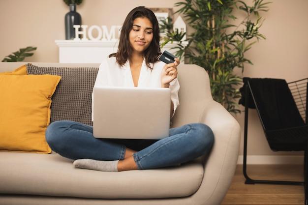 Frau, die auf sofa bleibt und eine kreditkarte hält