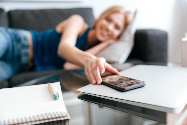 Frau, die auf sofa liegt und handy vom tisch nimmt