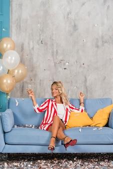 Frau, die auf sofa mit champagner sitzt