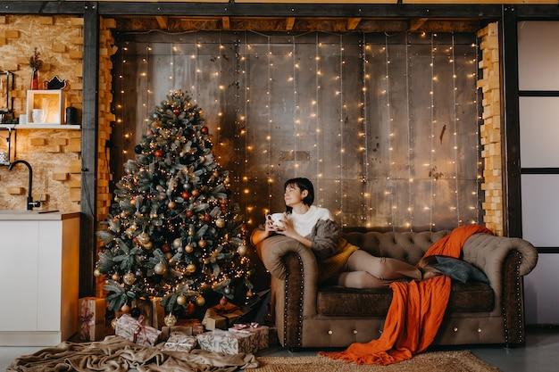 Frau, die auf sofa mit einer tasse kaffee oder tee neben einem weihnachtsbaum zu hause sitzt