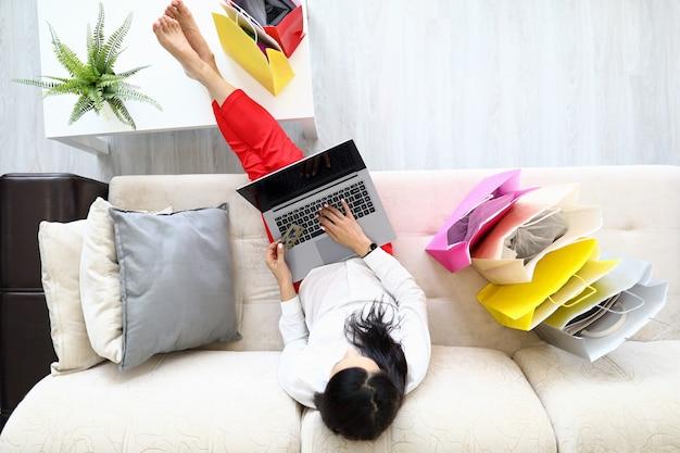 Frau, die auf sofa mit laptop- und kreditbankkarten-draufsicht sitzt
