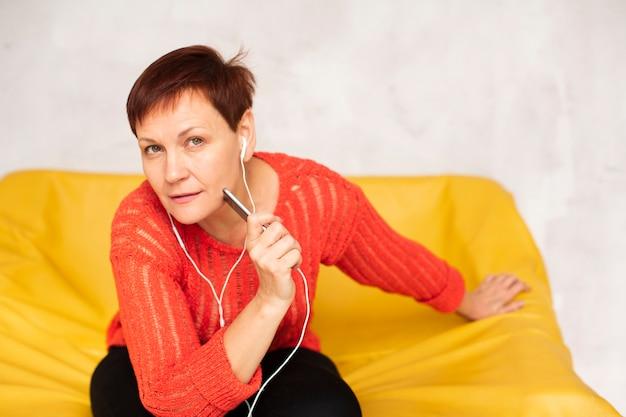 Frau, die auf sofa sitzt und fotografen betrachtet