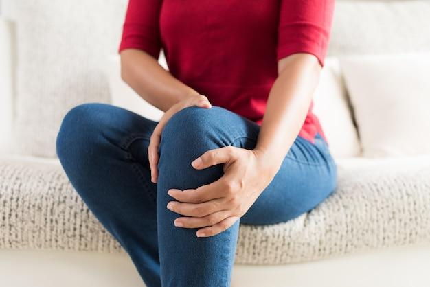 Frau, die auf sofa sitzt und knieschmerz fühlt. gesundheitskonzept.