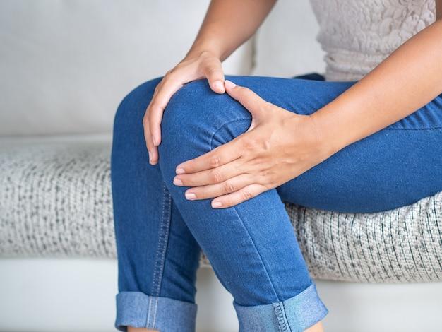 Frau, die auf sofa sitzt und knieschmerz fühlt