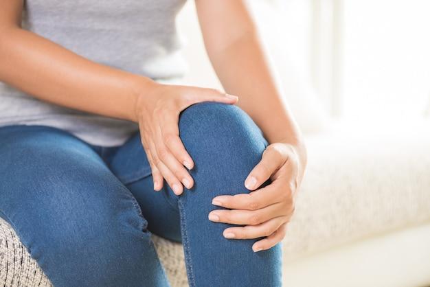 Frau, die auf sofa sitzt und knieschmerz, gesundheitswesen und medizinisches konzept glaubt.